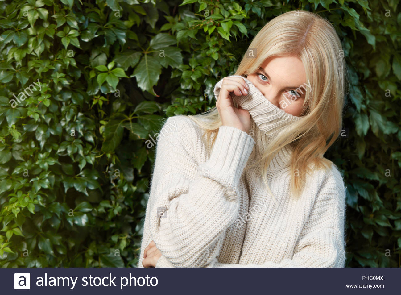 Young woman wearing sweater in front of hedge. - Stock Image
