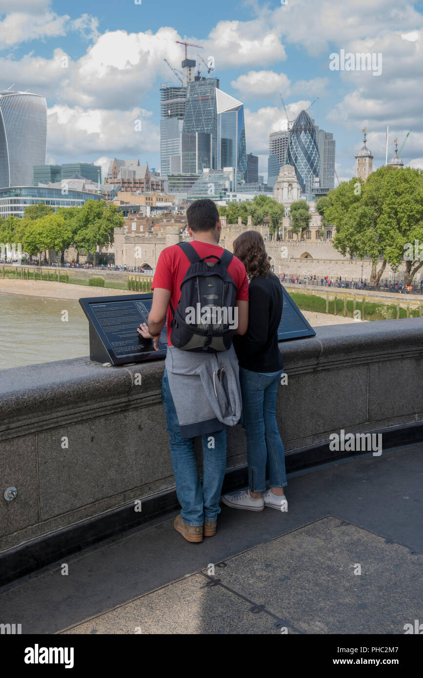 a young couple standing on tower bridge in central London looking at a tourist map with the city of London skyline behind them. - Stock Image