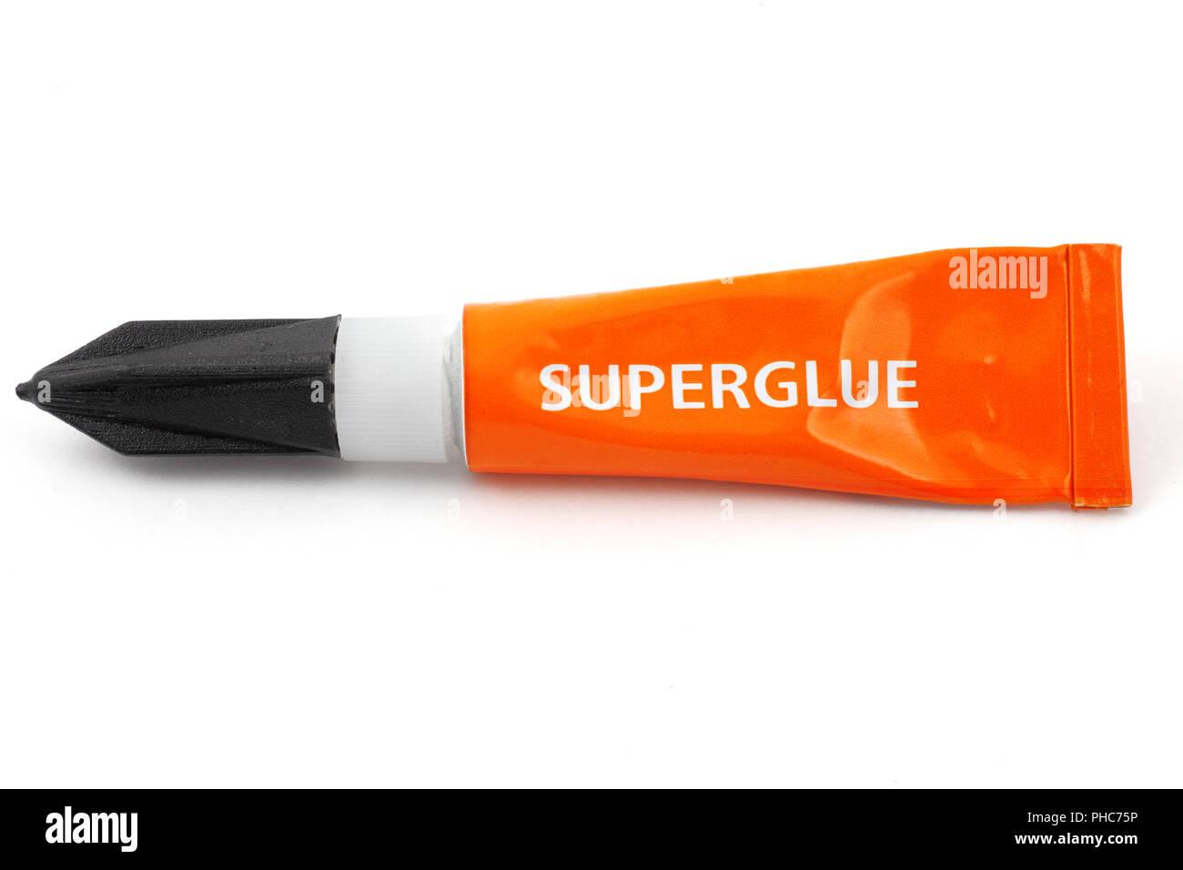 orange plastic tube labeled superglue - Stock Image