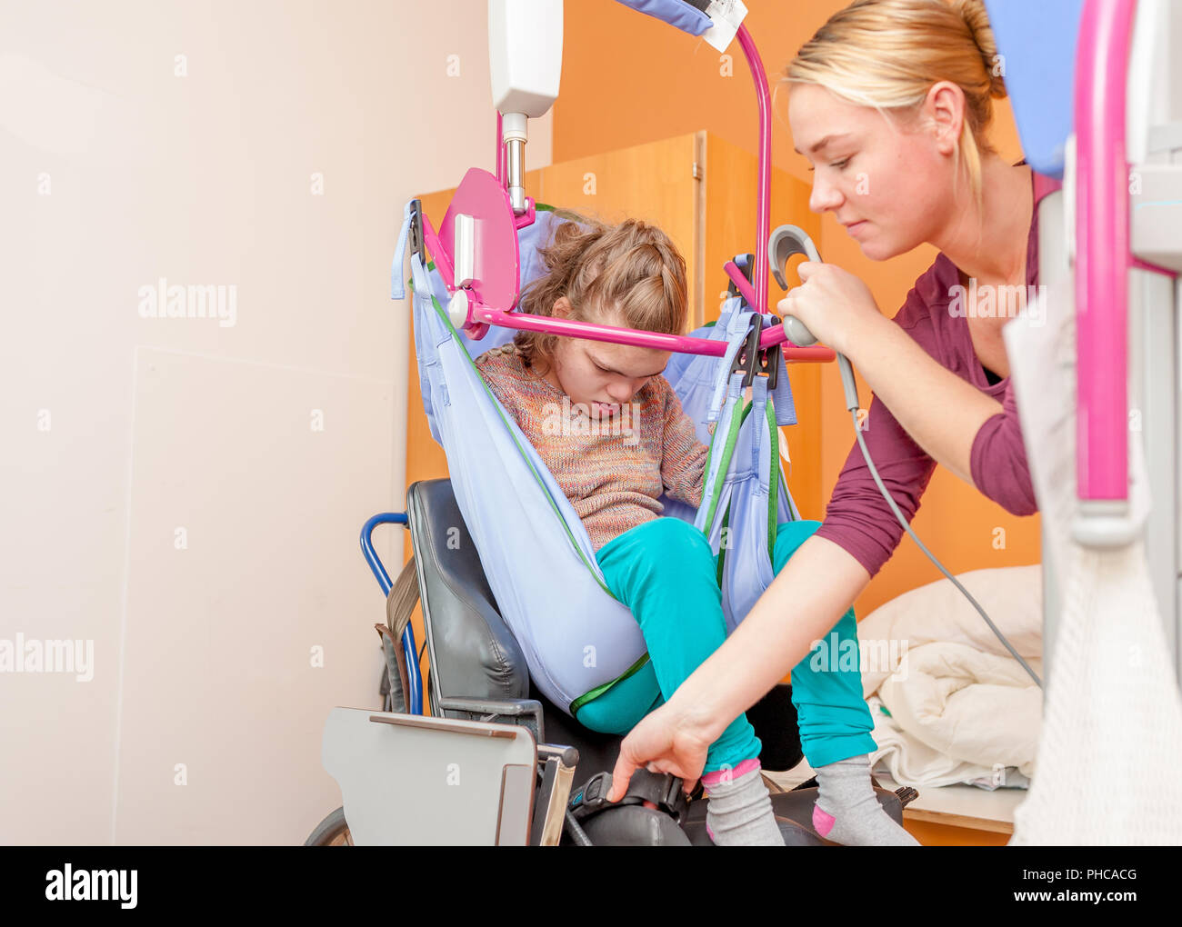 A disabled child being cared for by a special needs carer - Stock Image