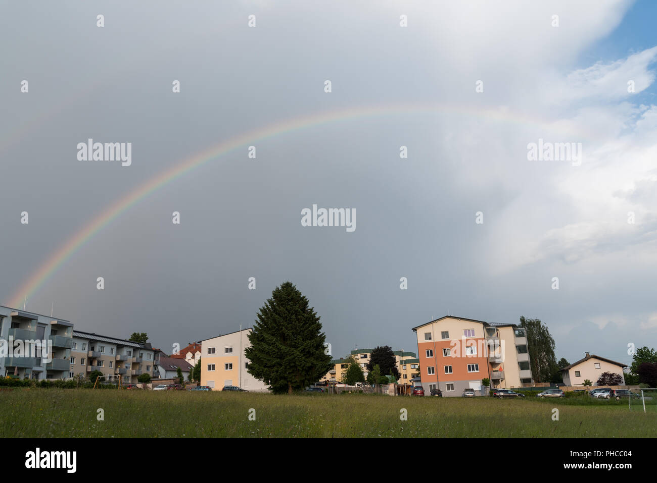 Bright rainbow in partly cloudy sky in the country - Stock Image
