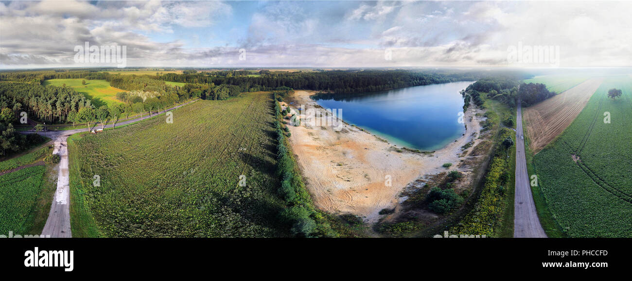 Panorama from aerial photos of a meadow and a lake - Stock Image