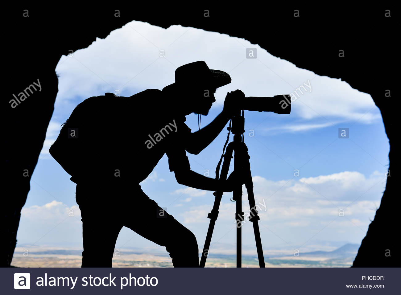 photographer and adventurer in the cave - Stock Image