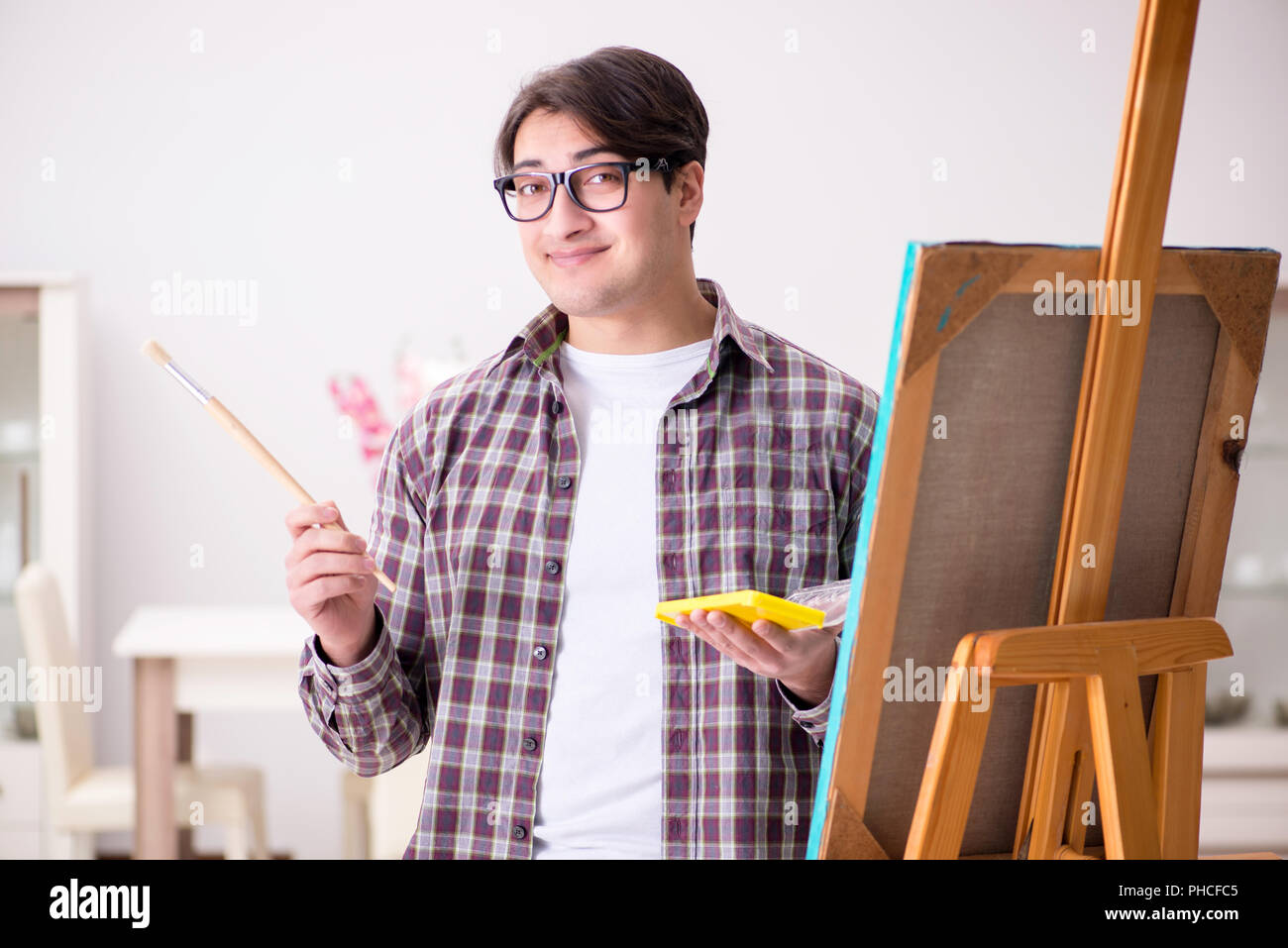 Young male artist drawing pictures in bright studio - Stock Image
