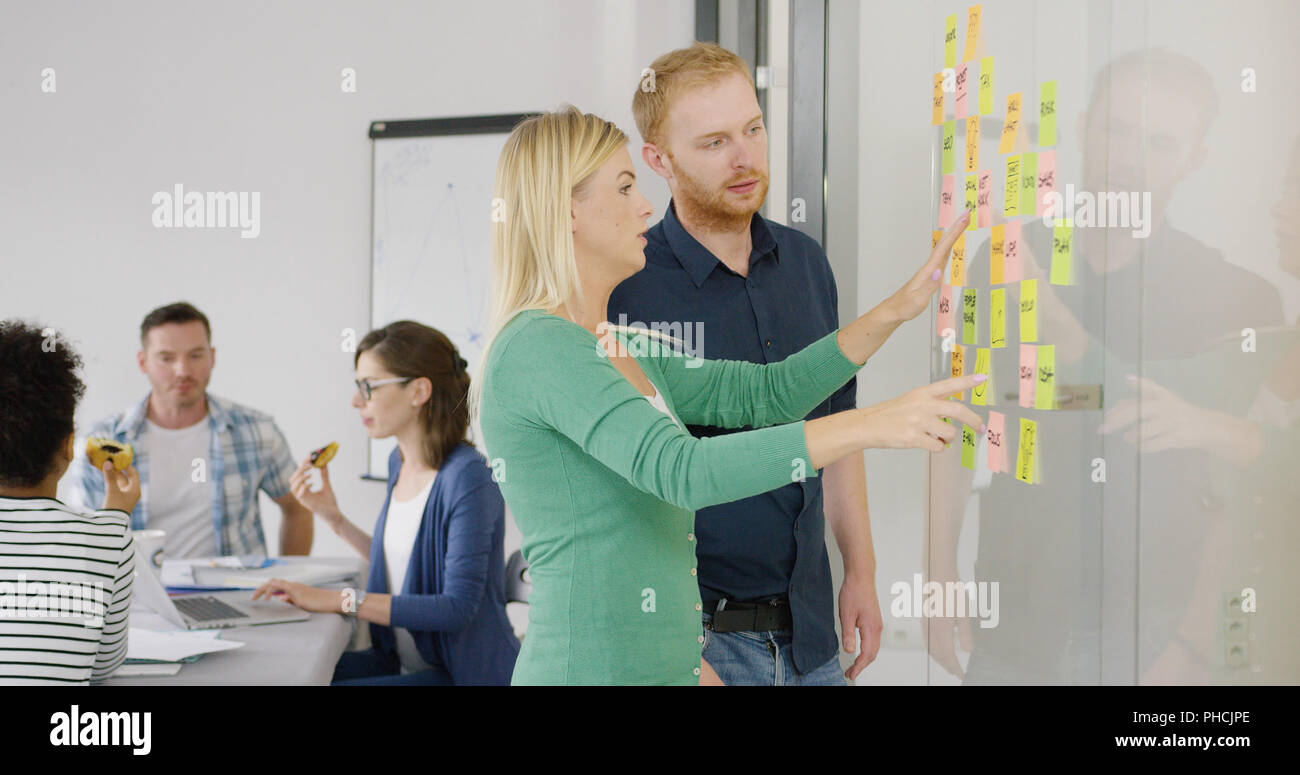 Two coworkers brainstorming on scheme Stock Photo