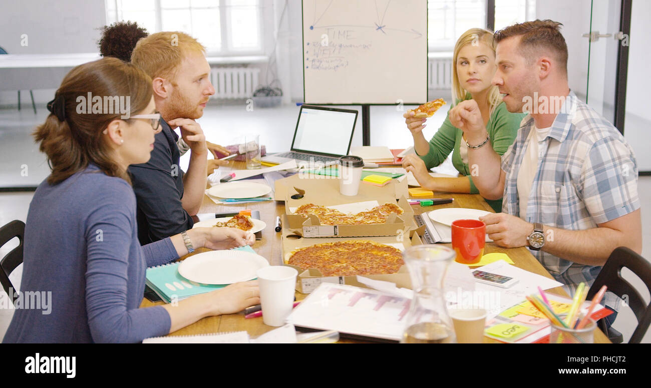 Young people enjoying pizza in office Stock Photo