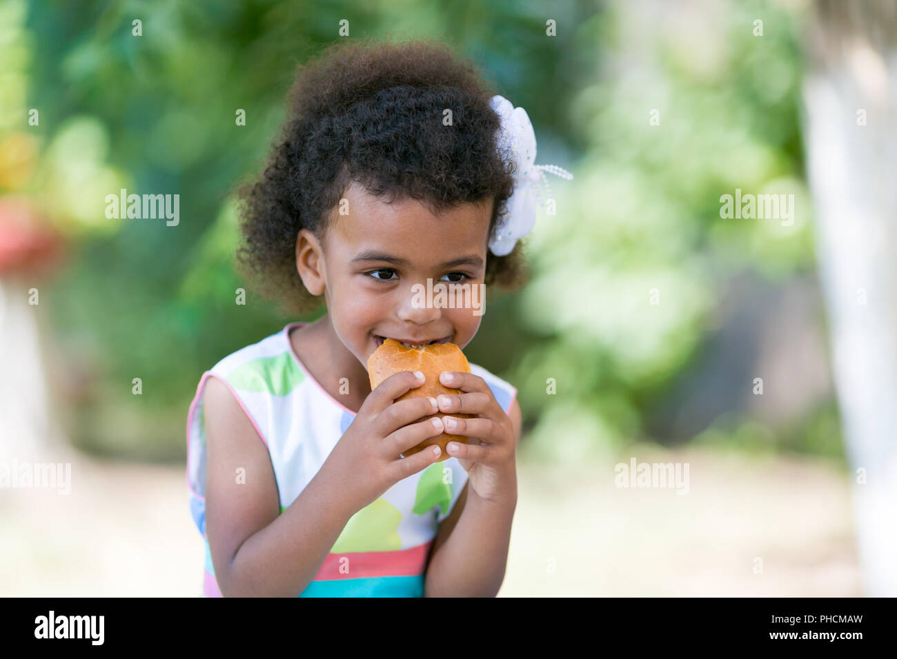 A beautiful 4 year old african american girl holding a two handed patty a