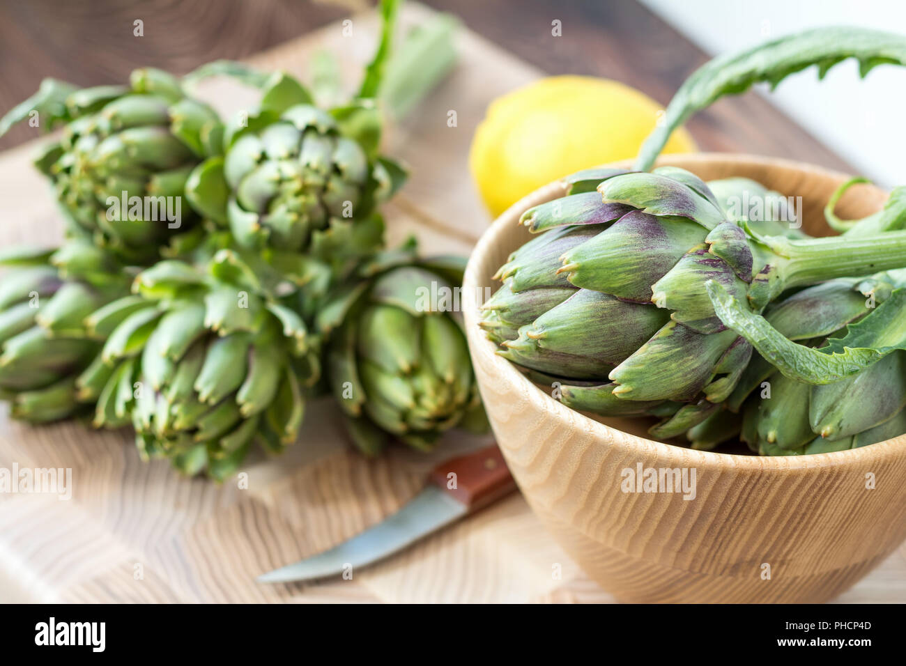 Two artichoke bouquets on kitchen table among some kitchen items - Stock Image