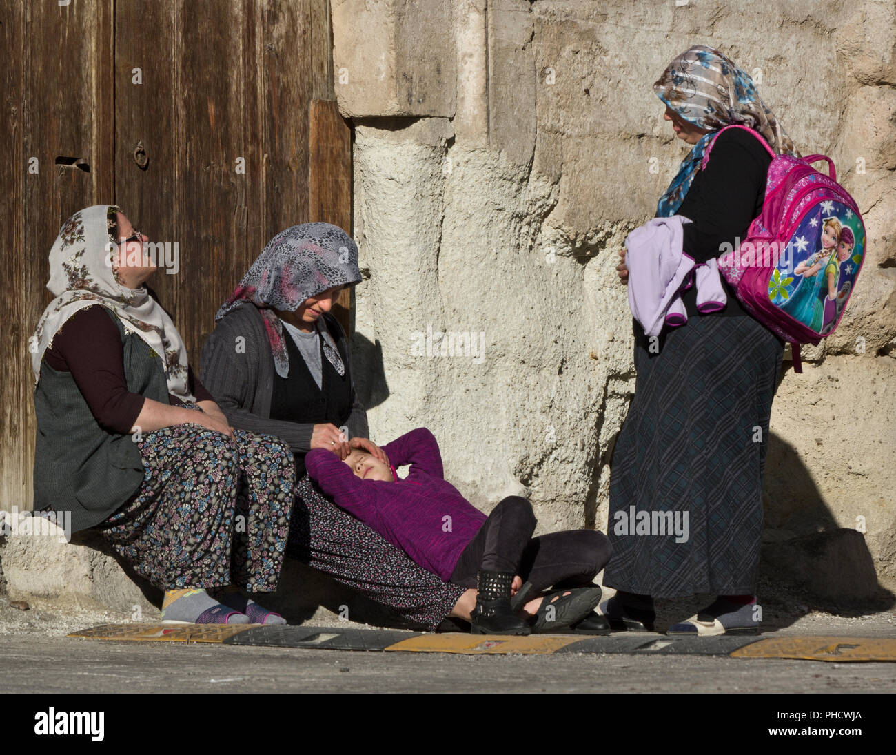Three Muslim women in hijabs and a girl relaxing and talking in the morning sun in Goreme, Turkey - Stock Image