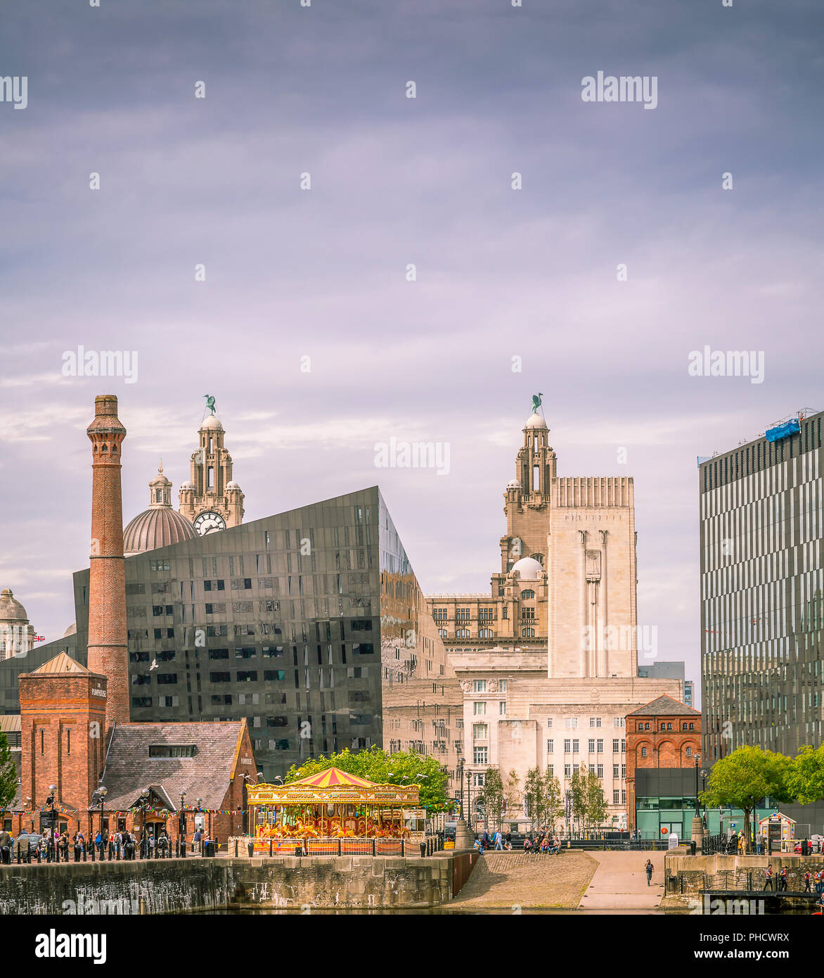 Looking across the dock in Liverpool towards the Royal Liver Building and Pumphouse. - Stock Image
