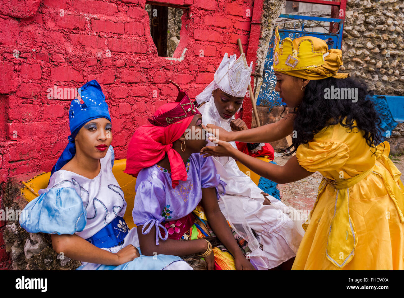 Havana, Cuba / March 20, 2016: Costumed Cuban women fixing makeup before Santeria performance at Hamel Alley. - Stock Image