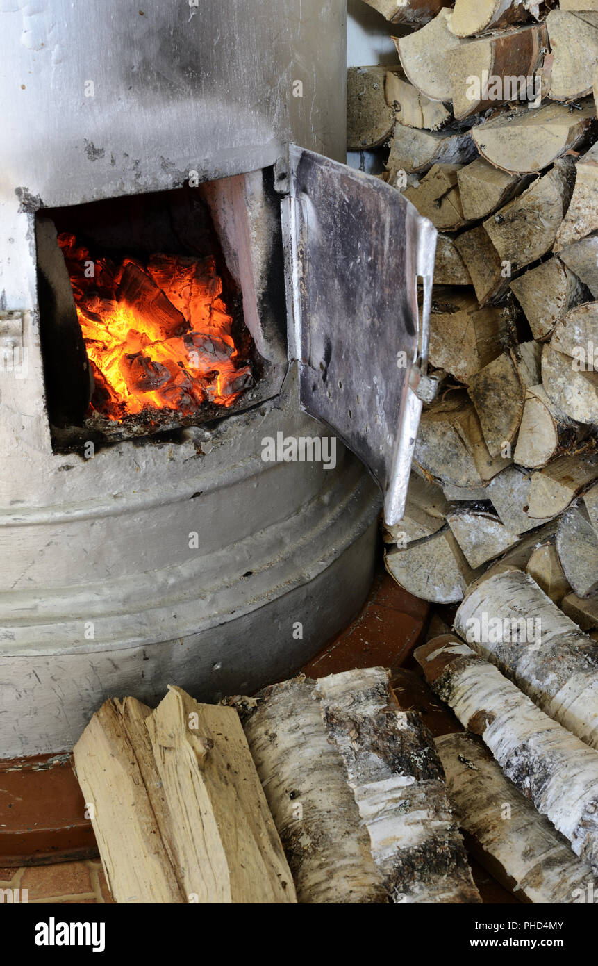 old stove flame and birch firewood - Stock Image