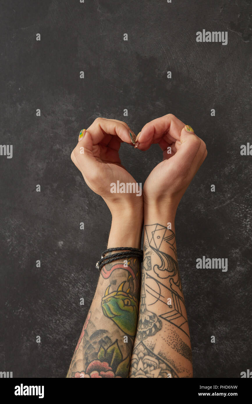 Female hands with tattoos in shape of heart - Stock Image