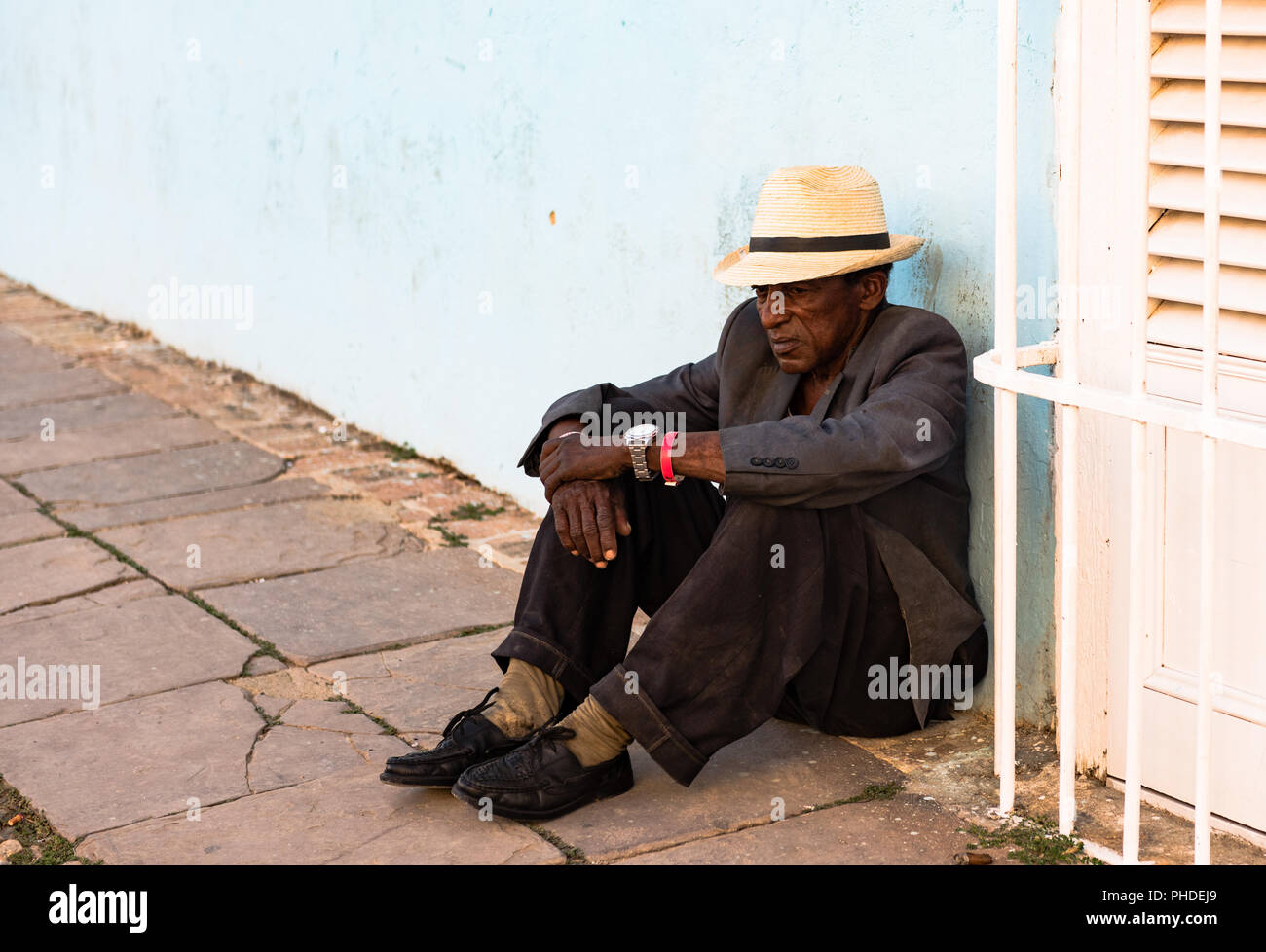 Trinidad / Cuba - March 15, 2016: Indigent Cuban man, wearing straw fedora and well-worn suit, sits on ground against blue wall in plaza square. - Stock Image