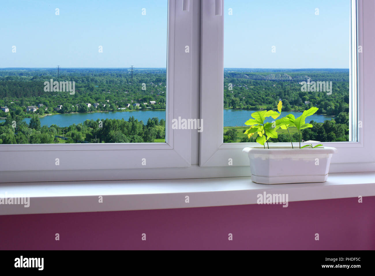 flower-pot on the window-sill and view to the country houses - Stock Image