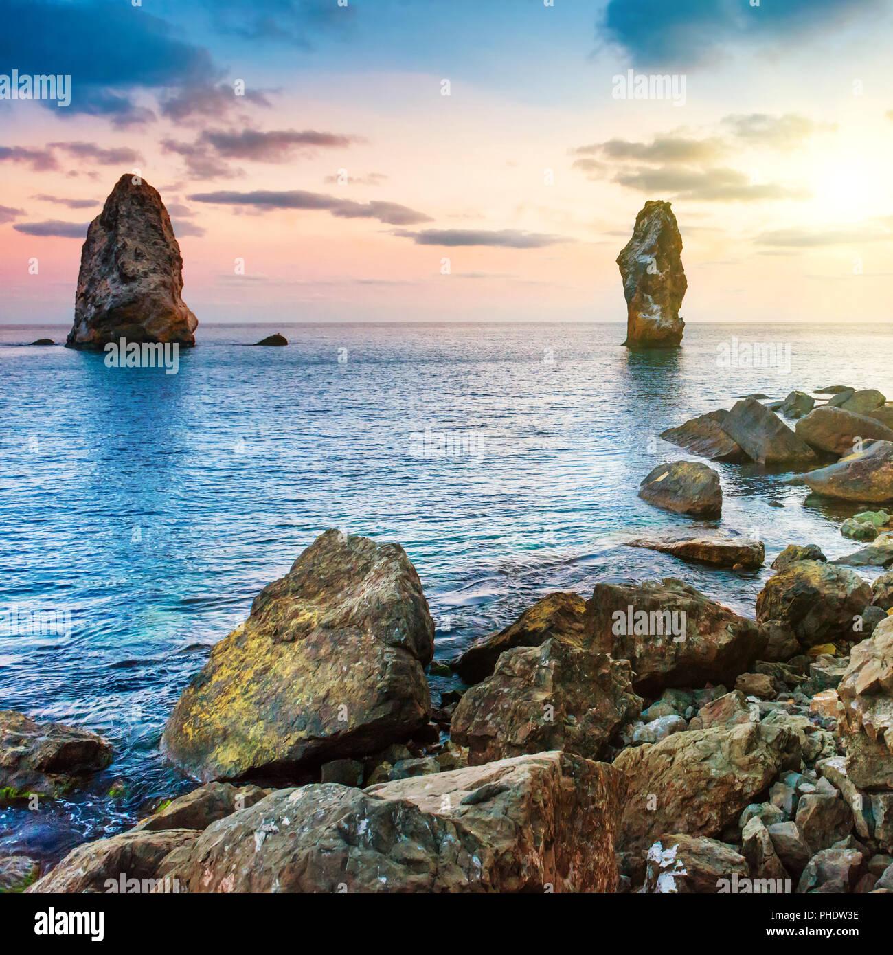 Sunset on the sea above big rocks - Stock Image