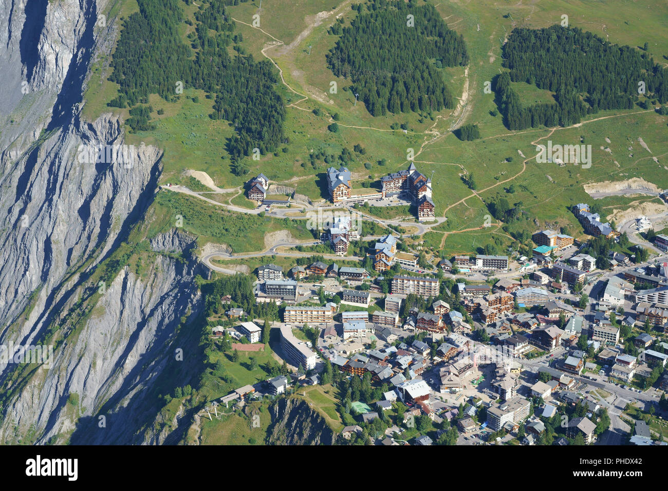 TOO CLOSE FOR COMFORT HEADWARD EROSON AT THE CITY'S LIMIT (aerial view). Ski resort of Les 2 Alpes in summer, France. - Stock Image