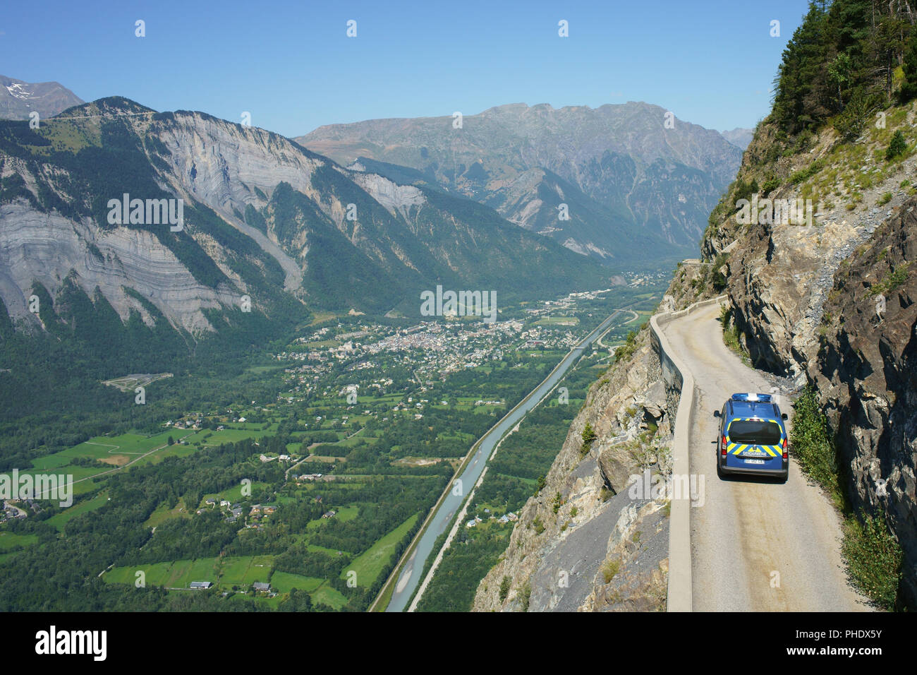 POLICE CAR CRUISING ON A CLIFF SIDE ROAD A STAGGERING 600 METER HIGH ABOVE THE VALLEY FLOOR (aerial view from a 6-meter mast). Auris, Isère, France. Stock Photo