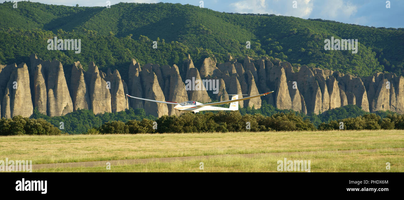 SAILPLANE ON FINAL APPROACH WITH THE ROCK FORMATION OF LES MÉES IN THE BACKGROUND. Chateau-Arnoux-Saint-Auban Airfield, Provence, France. - Stock Image