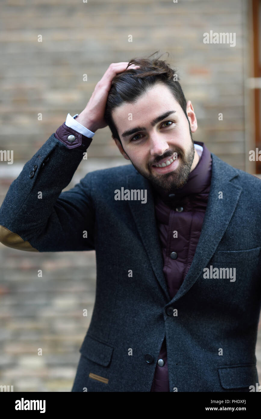 young bearded smiling man, model of fashion, in urban background