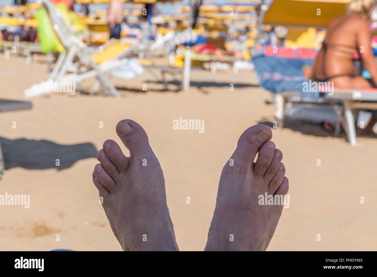 Feet on a sunbed at the beach - Stock Image