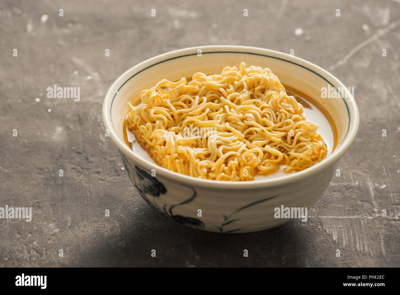 Instant noodles in bowl and vegetable side dishes on stone background. Quick & easy food concept. - Stock Image