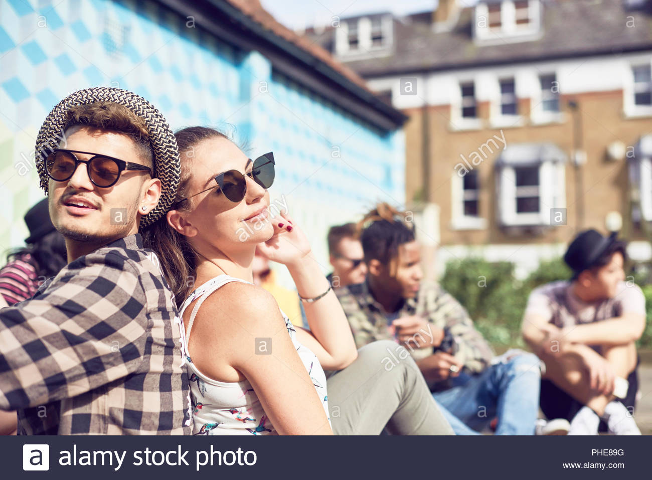 Teenage couple sitting back to back - Stock Image