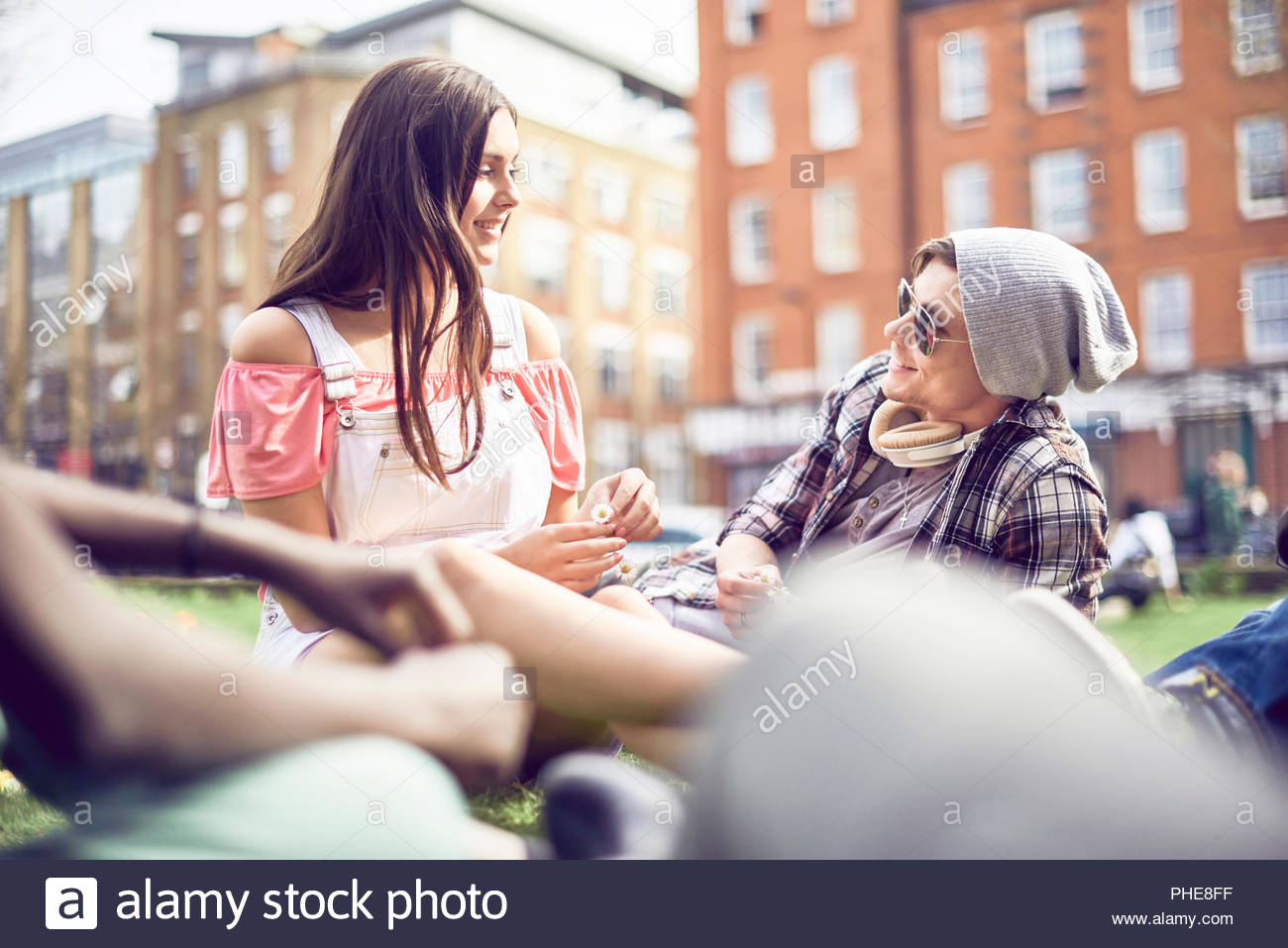 Teenage couple sitting at park - Stock Image