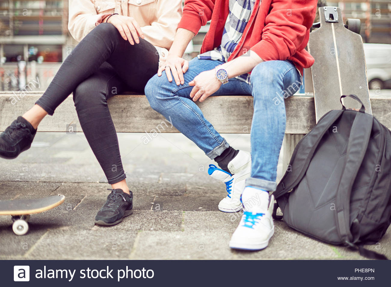 Legs of teenage couple sitting together - Stock Image