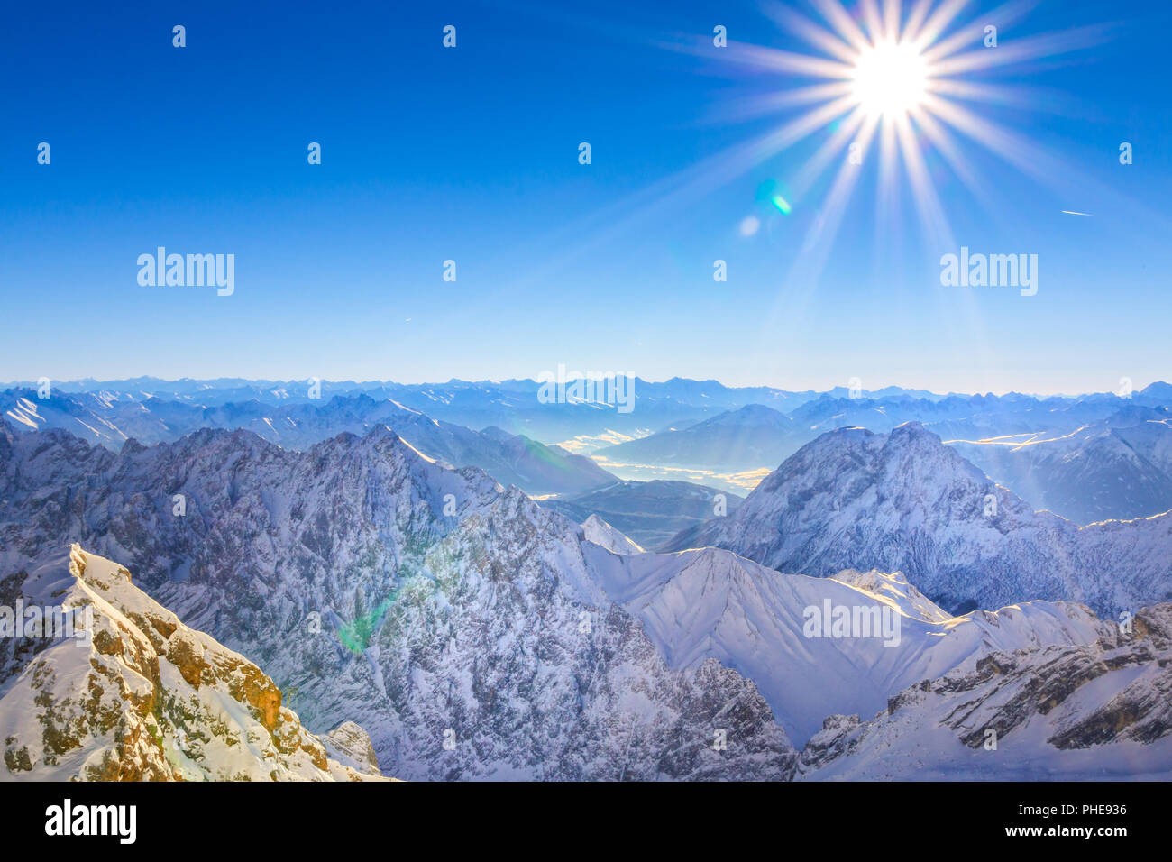 Ein Blick ins Tal vom höchsten Punkt Deutschlands, der Zugspitze. Der Blick geht über die sonnenbestrahlte Winterlandschaft im Wettersteingebirge. - Stock Image