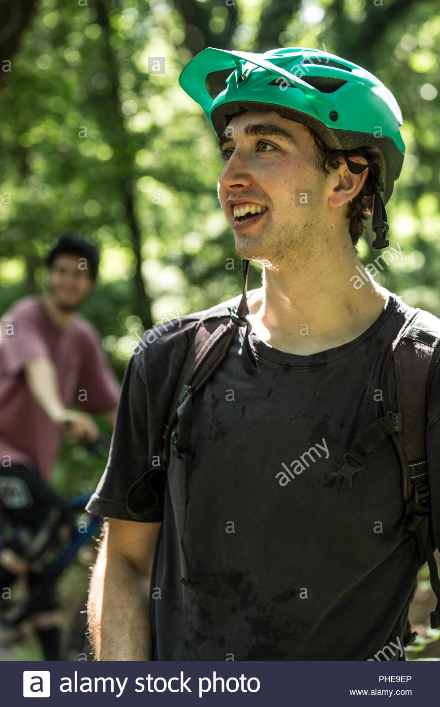 Young man wearing bicycle helmet in forest - Stock Image