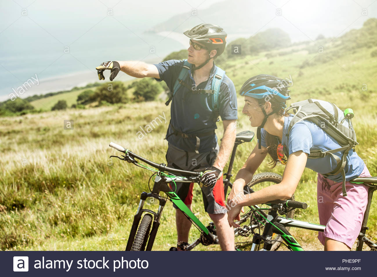 Couple wearing bicycle helmets on hill in Porlock Weir, England - Stock Image