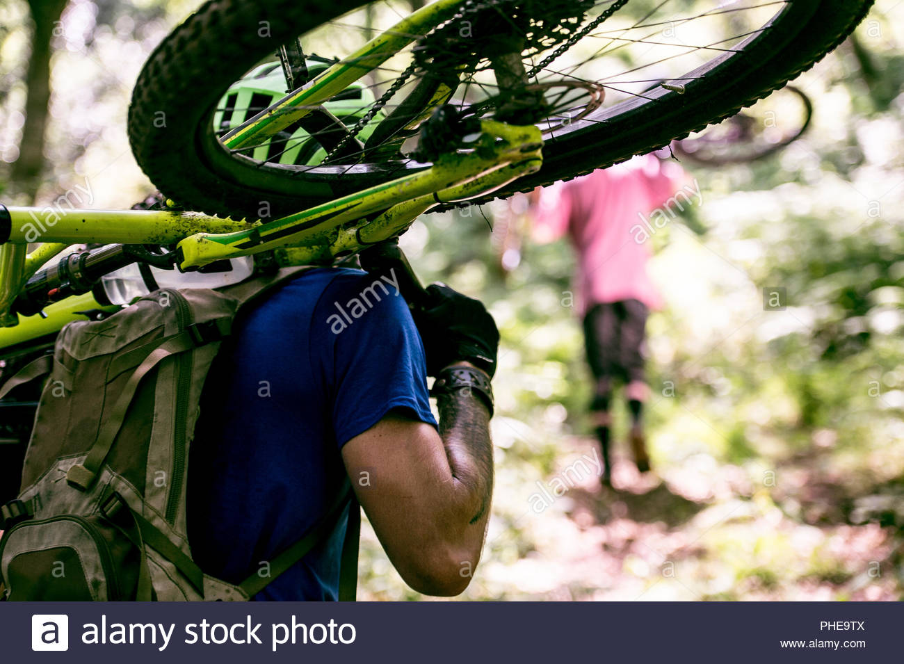 Man carrying his mountain bike in forest - Stock Image