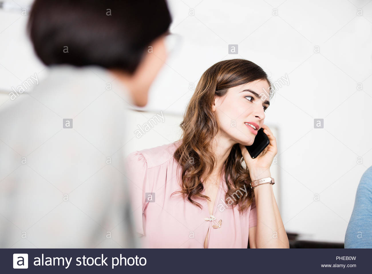 Young businesswoman talking on smartphone during meeting Stock Photo