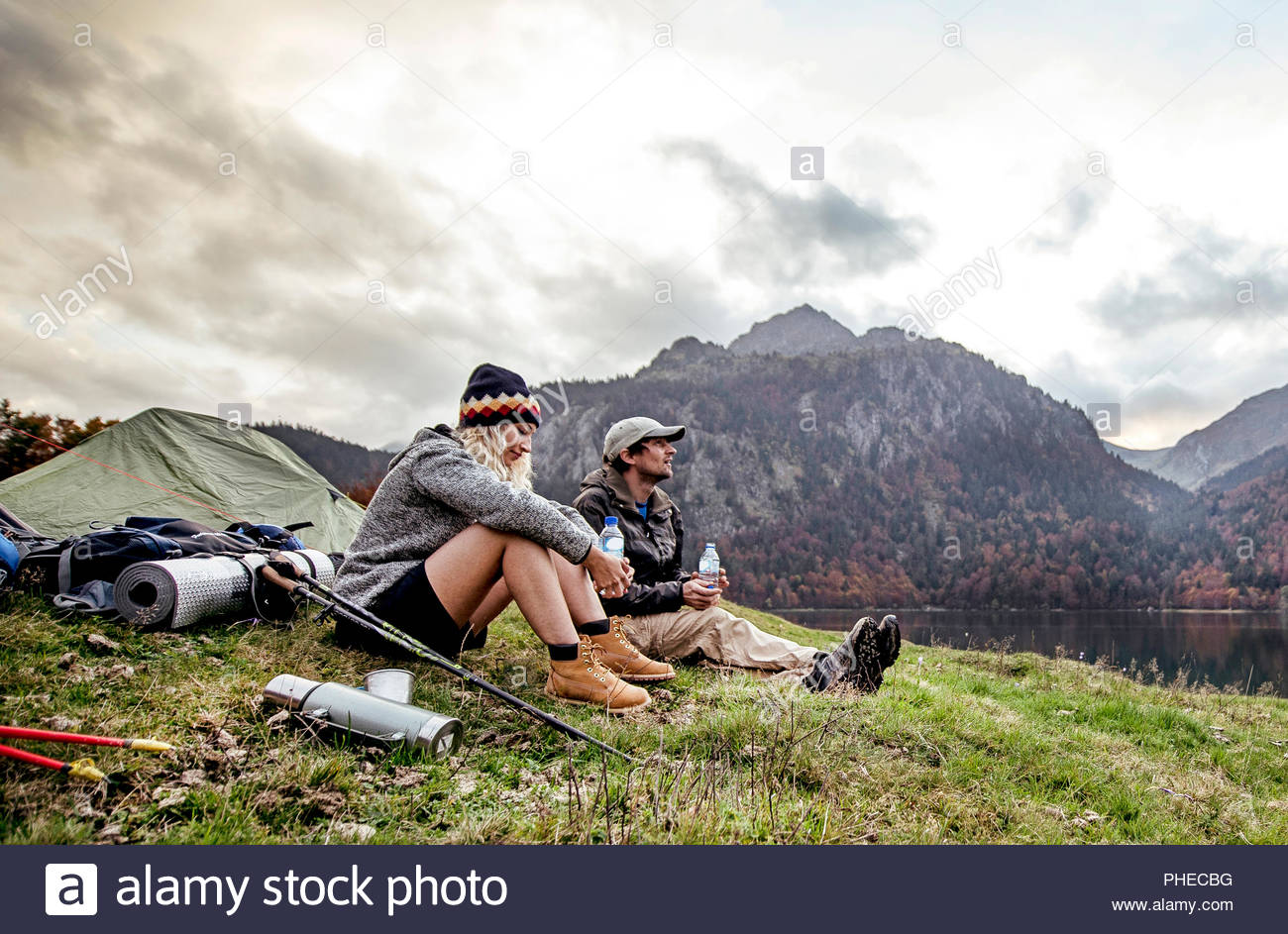 Young couple resting at camp beside mountains - Stock Image