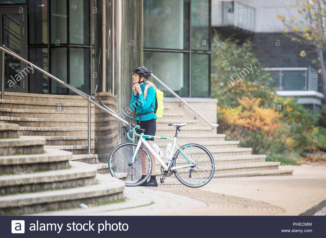 Woman removing helmet as she arrives to work by bicycle - Stock Image