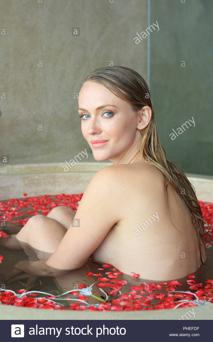 Young woman in bath with flower petals Stock Photo