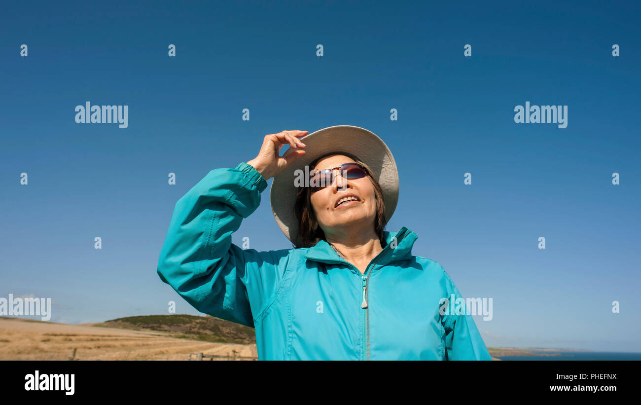 Mature, Asian lady wearing blue anorak, canvas hat and sunglasses, looks up to a clear blue sky with  facial expression to be interpreted. - Stock Image