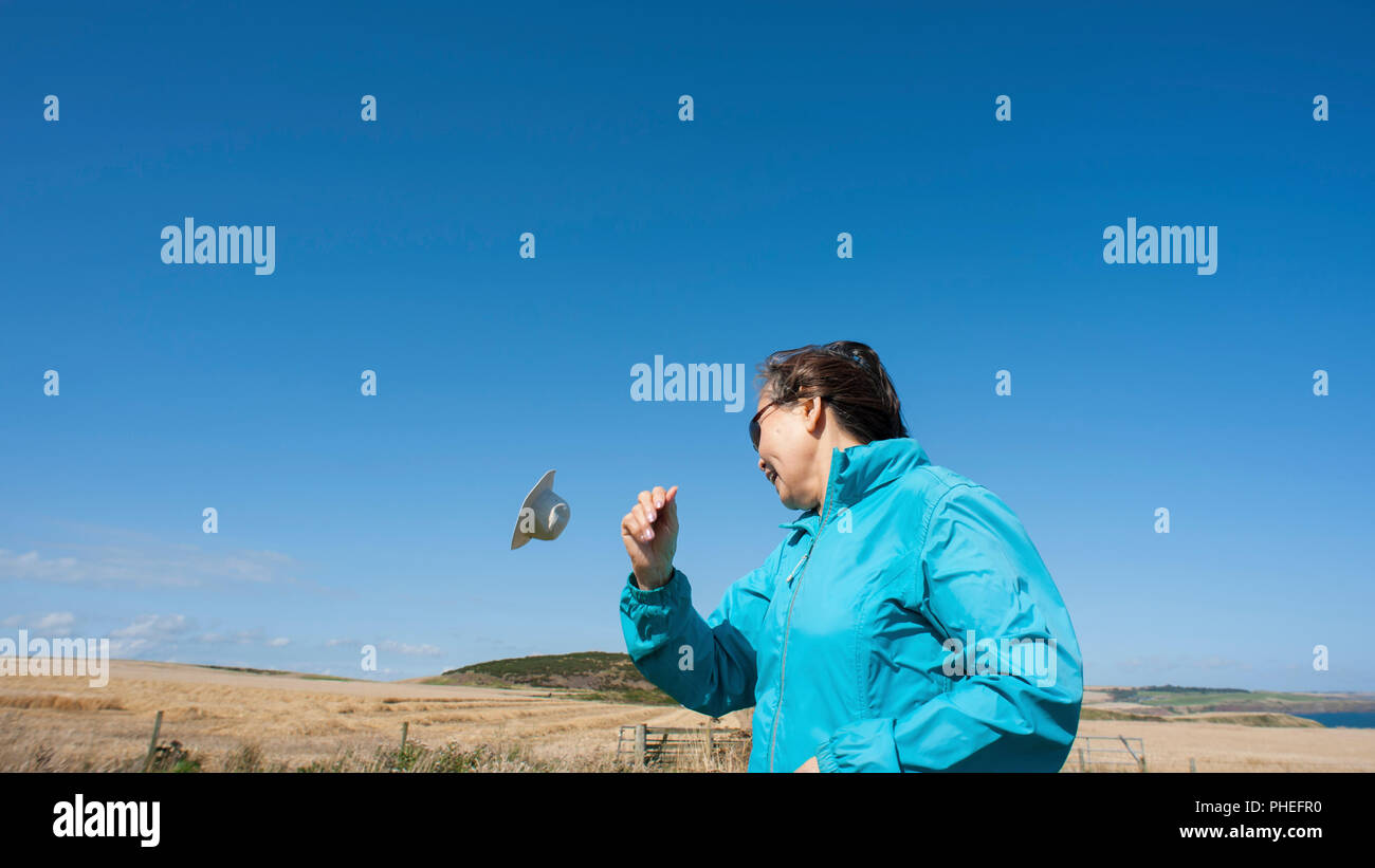 Attractive, Mature Asian lady wearing blue anorak, floppy canvas hat and sun glasses, has her hat blown off in strong wind. - Stock Image