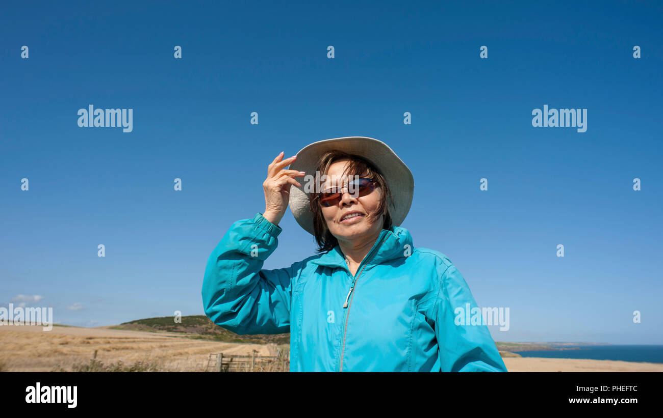 Attractive mature Asian lady wears blue anorak, canvas hat, sunglasses. Looks up to blue sky with  facial expression for interpretation. - Stock Image