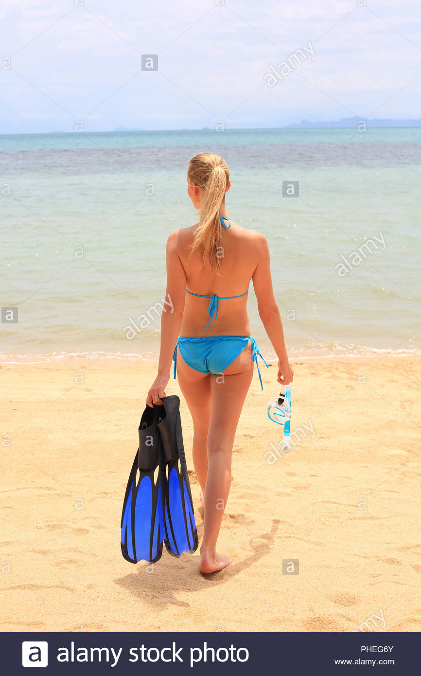 Young woman wearing bikini holding diving flippers on beach Stock Photo