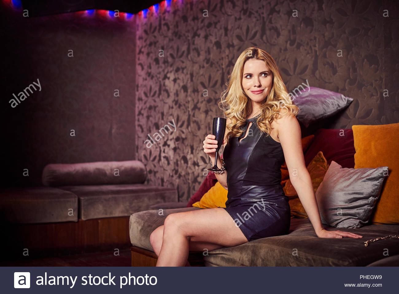 Young woman sitting on sofa at nightclub Stock Photo