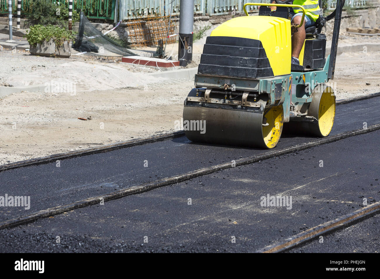 Steamroller construct asphalt road and railroad lines - Stock Image