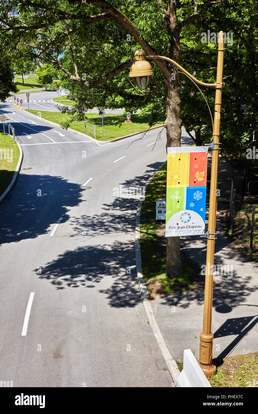 Road junction, lamp post and the banner of Jean Drapeau Park (parc jean drapeau) on Saint Helen's island in Montreal, Quebec, Canada. Stock Photo