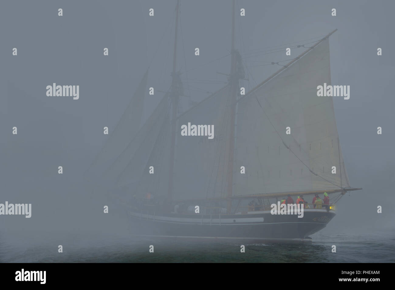 Two masted Schooner with sails on port-side tack sails into dense fog Stock Photo