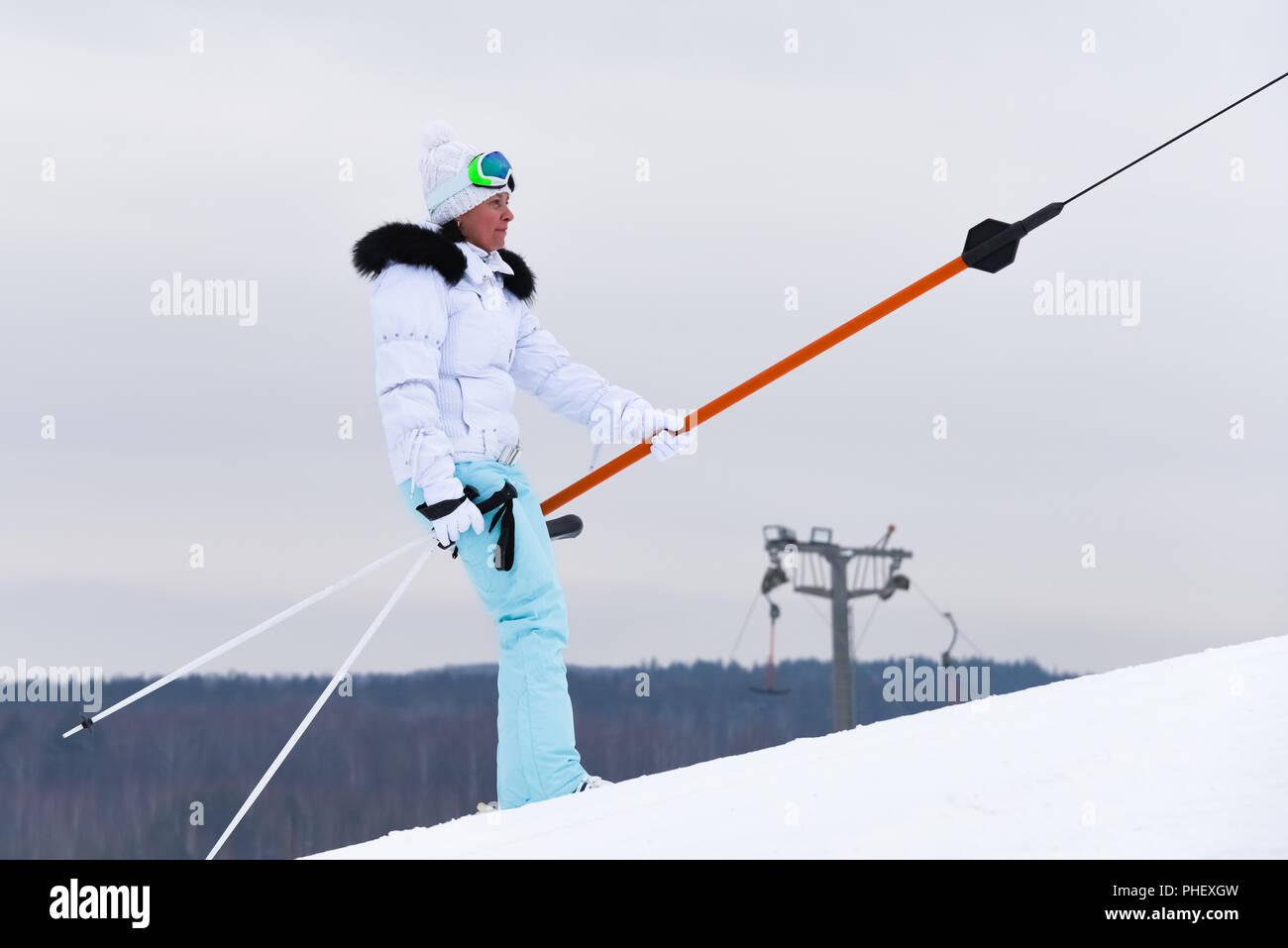 a woman skiing a mountain resort on a ski lift - Stock Image