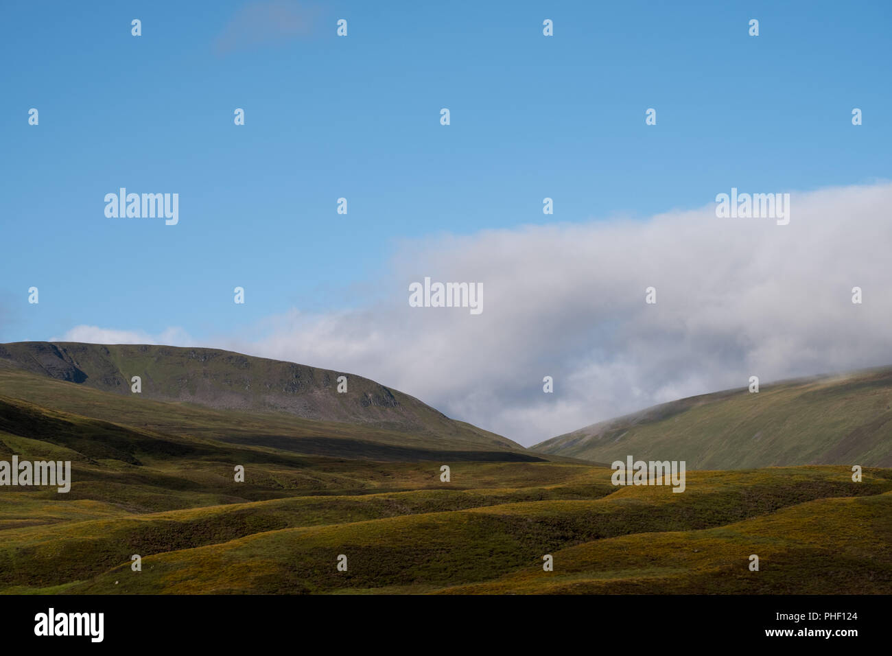 Hills in Scottish Highlands on a clear summer's day, with low lying cloud. Photographed early in morning near Inverness from Caledonia Sleeper train. - Stock Image
