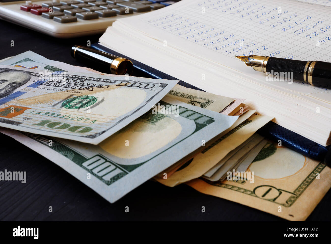 Ledger, calculator and dollar banknotes. Bookkeeping. - Stock Image