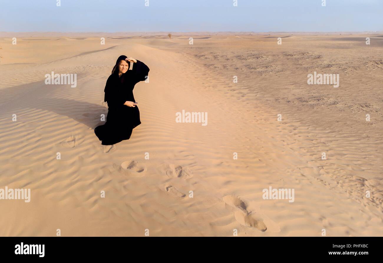 woman in a traditional emirati dress called abaya in a desert near Dubai Stock Photo