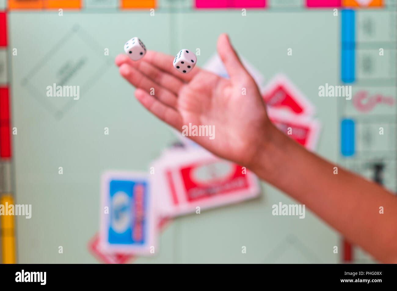 The hand throws game dice on the background of the playing field Stock Photo